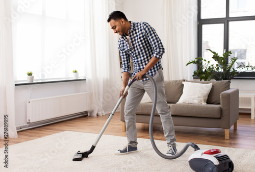 Fotografía  household and cleaning concept - indian man with vacuum cleaner at home