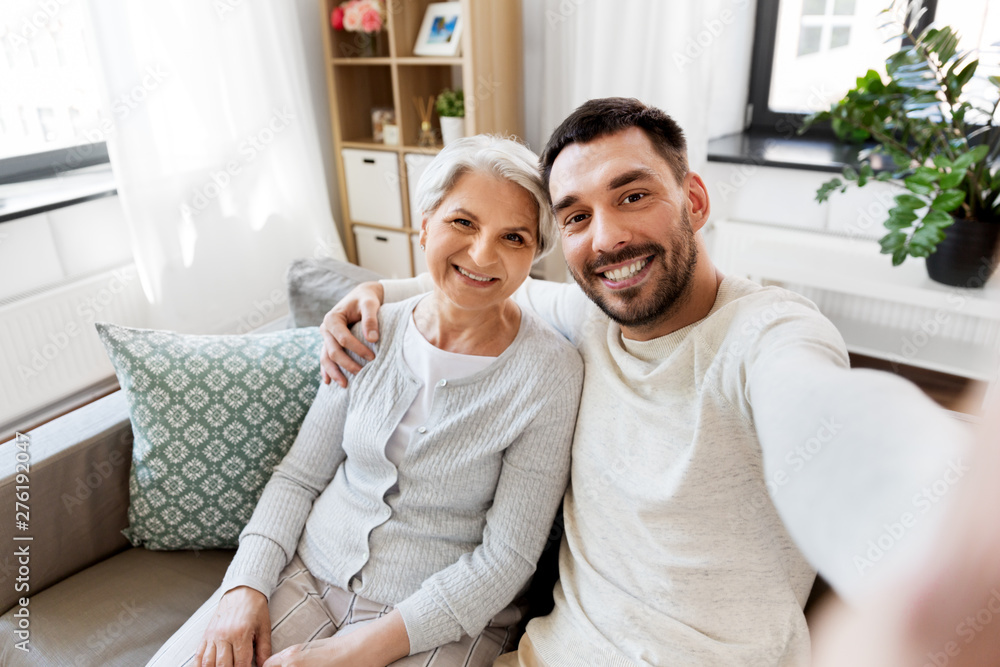 Fototapeta family, generation and people concept - happy smiling senior mother with adult son taking selfie at home