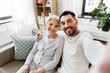 family, generation and people concept - happy smiling senior mother with adult son taking selfie at home