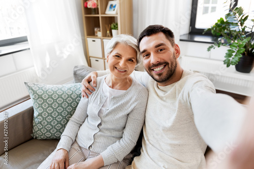 Fototapeta family, generation and people concept - happy smiling senior mother with adult s