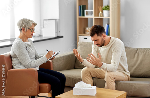 Deurstickers Snelle auto s psychology, mental therapy and problem concept - senior woman psychologist taking notes to notebook and sad young man patient at psychotherapy session