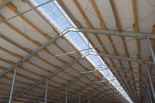 Roof Structure Consisting Of A Metal Frame, Wooden Beams And Foam Insulation Against A Blue Sky. Agricultural Constructions. The Roof Of The New Barn.