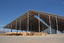 Construction Of Agricultural Facilities. Wooden Beams For The Construction Of The Roof Against The Background Of A Village Hangar Under Construction