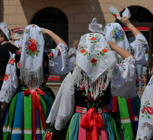 Girl In Traditional Costume From Lowicz Region In Poalnd Stand On Their Back Waving Handkerchief