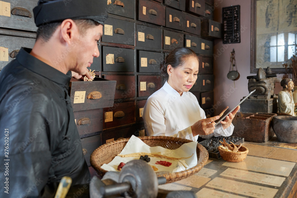 Fototapeta Asian practitioners working in traditional old apothecary and making remedies out of dry herbs and roots