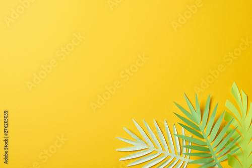 Cuadros en Lienzo top view of paper cut exotic green palm leaves on yellow background with copy sp