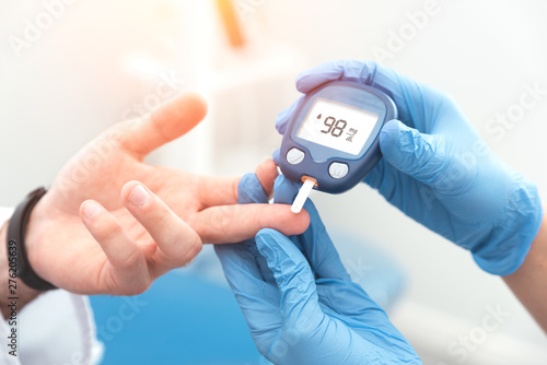 Foto  Doctor checking blood sugar level with glucometer