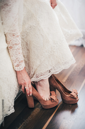 Fototapeta  hand puts a wedding brown shoes on his leg