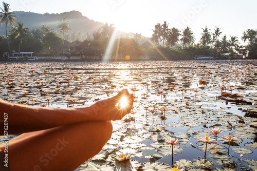 Fotografia  Woman practices yoga on a lake with lotus water lilies