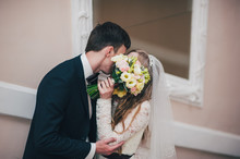 A Stylish Elegant Bride With Bouquet Of Wedding Flowers Stands Near The Mirror. Kisses. The Bouquet Closed His Face, Hid Newlyweds. Hugs. Close Up. Portrait. Retro. Vintage Architecture Indoors.
