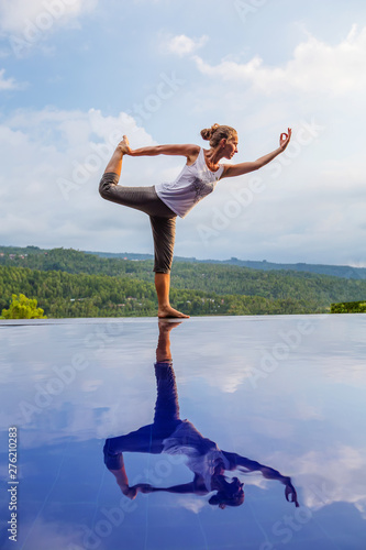Fotografia  Caucasian woman practicing yoga by the pool