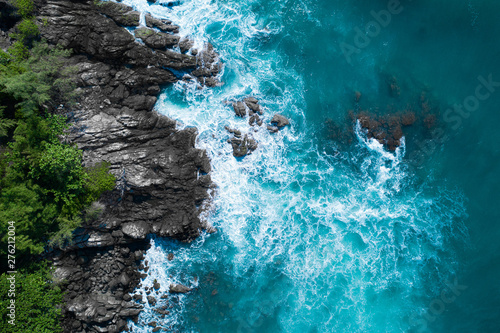 Tablou Canvas Aerial drone top view of ocean's beautiful waves crashing on the rocky island co