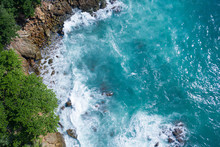Aerial Drone Top View Of Ocean's Beautiful Waves Crashing On The Rocky Island Coast With Green Trees