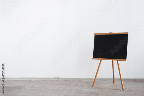 Photo  Blackboard on a white wall background with copy space.