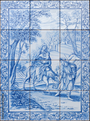 CATANIA, ITALY - APRIL 8, 2018: The ceramic tiled Flight to Egypt scene on the facade of Curia Arcivescovile by F. Fodinlio from 20. cent.