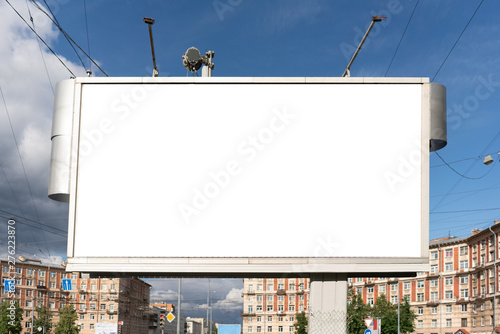 billboard 3 by 6 meters standing in the city. White advertising big space for design placement. on a nice summer day with blue sky