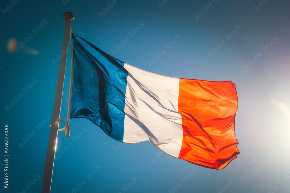 Fototapety, obrazy: Looking up to a beautiful waving french flag against a blue sky with sunlight.