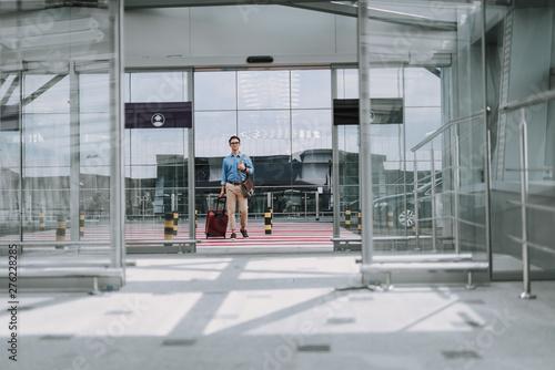 Cuadros en Lienzo Young male in glasses with bag walking along crosswalk