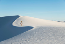 Woman Walking Along A White Sand Dune, Cast In Blue Late-afternoon Light, In White Sands National Monument, New Mexico
