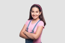 Portrait Of Happy Beautiful Brunette Young Girl In Casual Pink T-shirt And Blue Overalls Standing, Looking At Camera With Toothy Smile And Crossed Arms. Indoor Studio Shot, Isolated On Gray Background