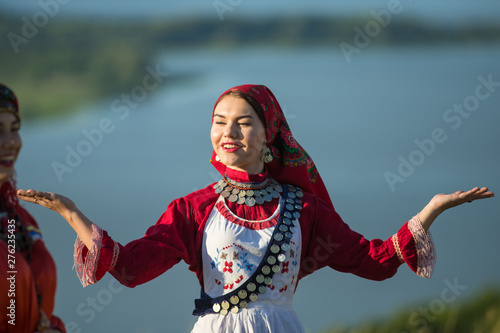 Young smiling woman in traditional russian clothes dancing on the field Canvas Print