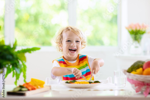 Fotografiet Baby eating vegetables. Solid food for infant.