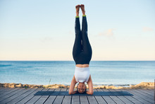 Beautiful Fit Woman Practicing Yoga Against Blue Sea Standing In Headstand Pose.