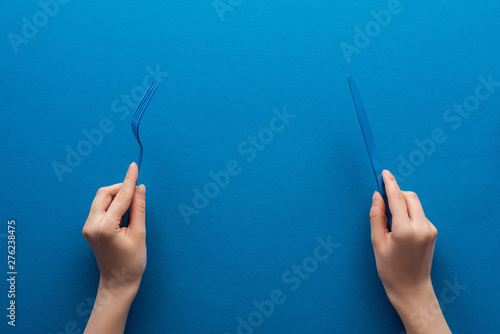 Obraz cropped view of woman holding blue plastic fork and knife on blue background - fototapety do salonu
