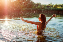 Young Woman In Bikini Playing In Water And Making Splash. Summer Vacation