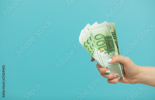 Photo  Female hands holding euro banknotes on a blue background.