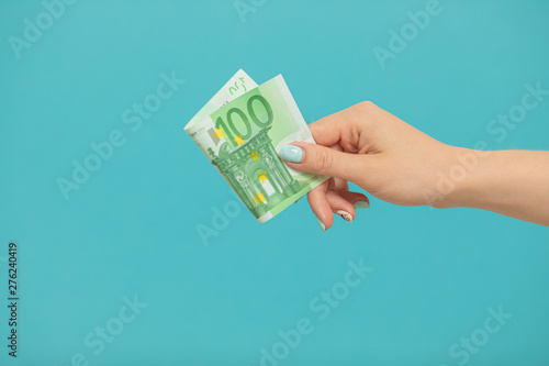 Fototapeta Female hands holding euro banknotes on a blue background. obraz