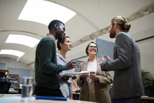 Low Angle View At Multi -ethnic Group Of Business People Laughing Happily While Chatting During Coffee Break In Office, Copy Space