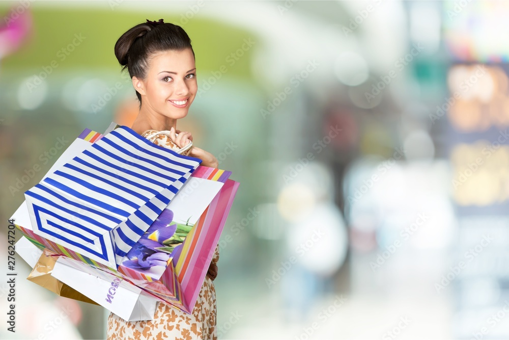 Fototapety, obrazy: Young woman with shopping bags on  background