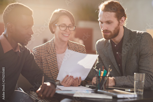 Warm toned portrait of group of business people working in cafe lit by sunlight Slika na platnu
