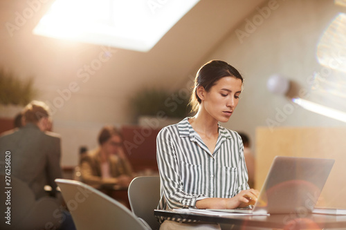 Deurstickers Graffiti collage Warm-toned portrait of young businesswoman using laptop sitting at table in cafe, copy space