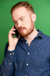 Portrait of young Irish serious man in deep blue denim shirt calling on phone