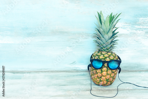 Poster de jardin Magasin de musique Ripe pineapple with blue mirror sunglasses and headphones in front of a blue wooden rustic background.