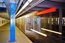Silver New York Subway Express Train Bulleting Through Subway Station With Abstract Lighting