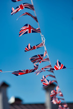 Union Jack Flag Bunting Tied To A Tree, Flying In The Wind Against A Blue Sky