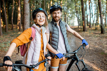 Portrait Of A Young Couple Dressed Casually Standing Together With Mountain Bicycles, Traveling In The Forest During The Summer Vacations