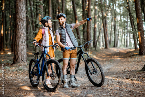 Young couple dressed casually standing together with mountain bicycles, travelin Wallpaper Mural