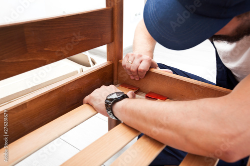 The man is assembling wooden furniture in home Canvas Print
