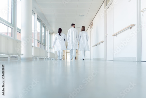 Stampa su Tela  Three doctors walking down a corridor in hospital