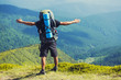 A man tourist walks along a mountain meandering trail. Summer walking in mountains