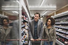 Couple Choosing A Ready Meal In Grocery Store