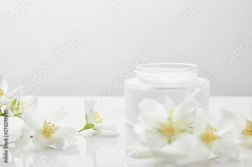 Cadres-photo bureau Fleuriste jasmine flowers on white surface near jar with cream