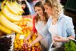 Leinwandbild Motiv Young happy women shopping vegetables and fruits on the market