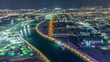 canvas print picture - Dubai water canal with footbridge aerial night timelapse from Downtown skyscrapers rooftop
