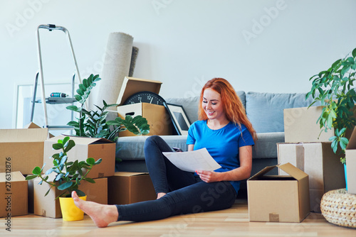 Poster Individuel Young woman sitting on floor in new apartment with smartphone and documents