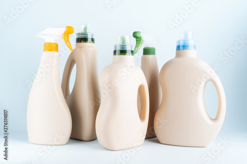 Obraz Сlose-up of cleaning products on blue white background overview with space for text. Front view. Cleaning tools layout.  Blank mockup Eco Design of plastic bottles packaging of detergent. - fototapety do salonu